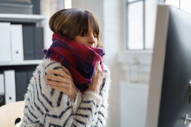 Young woman with fever wrapped up in scarf to stay warm