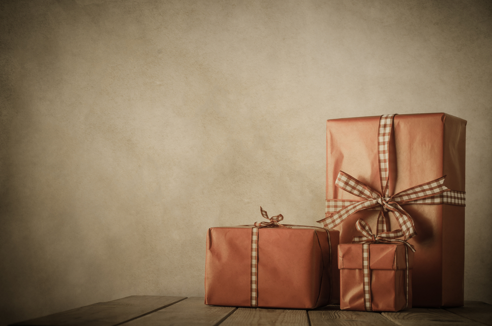 3 Christmas presents wrapped in brown paper with ribbon