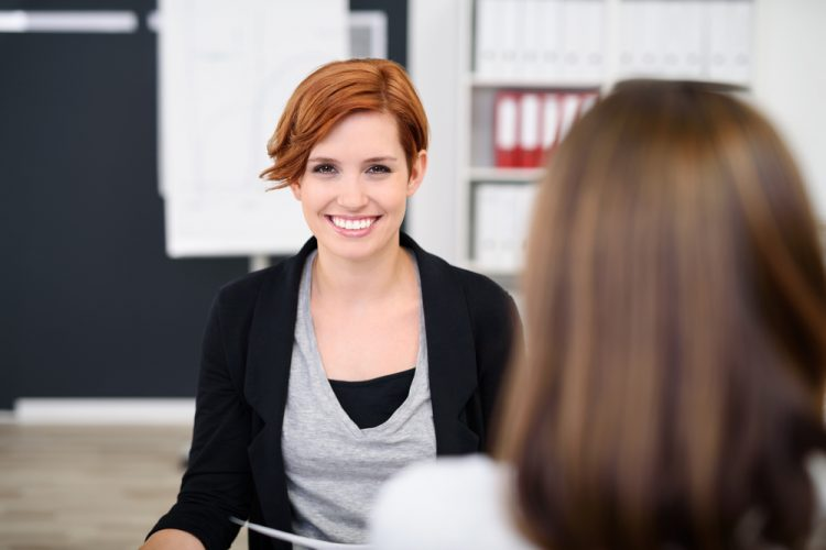 Two young women meeting - a return to work interview at the office
