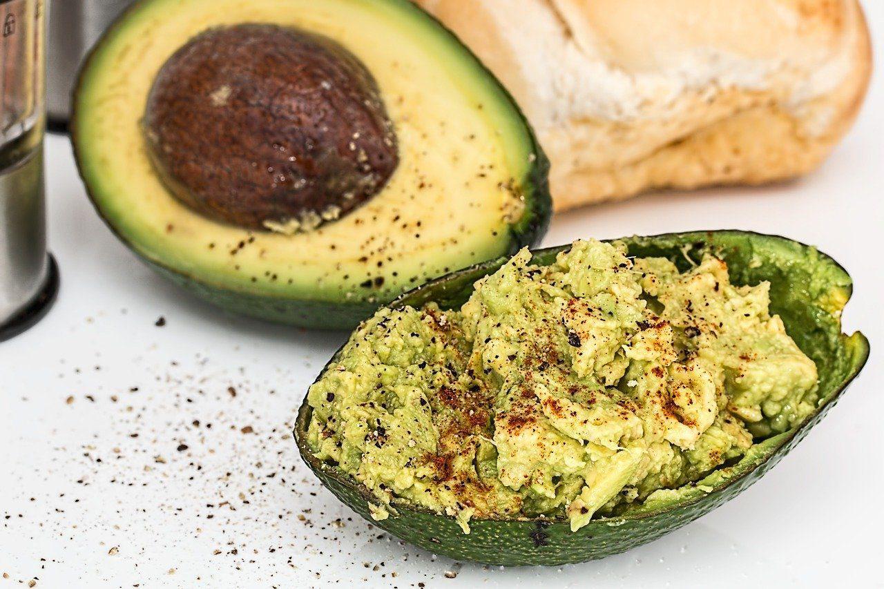 Healthy avocado snack half filled with guacamole