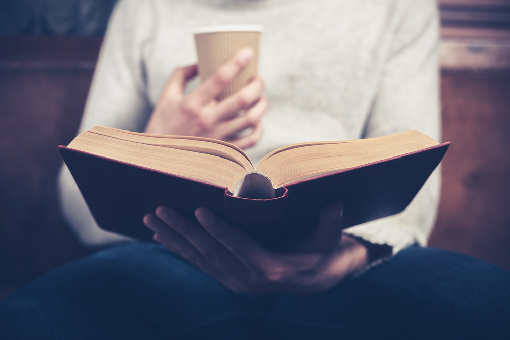 Man reading business book with a hot drink