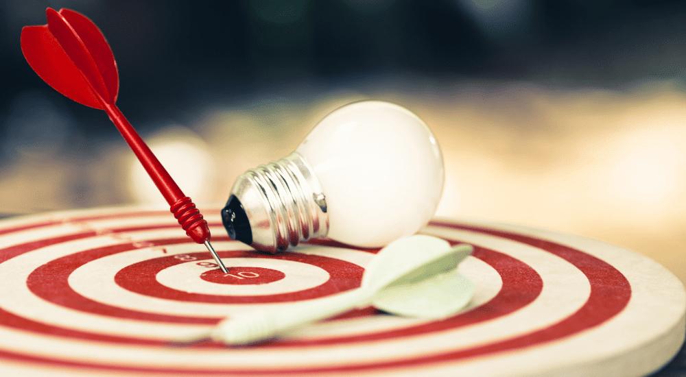 Setting goals concept - dartboard, lightbulbs, ideas