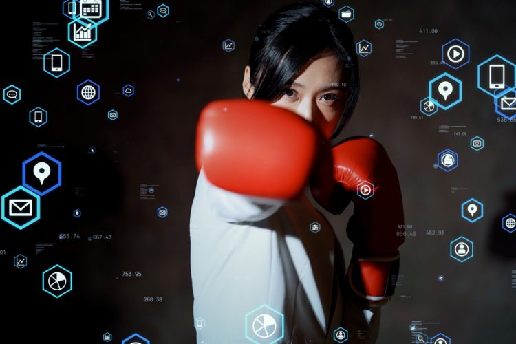 Concept - young Asian woman in boxing gloves - punch for growth